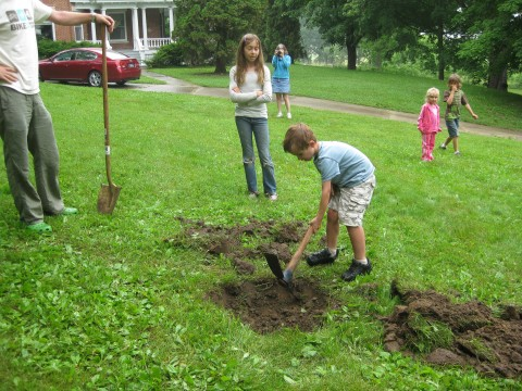 Daniel Steussy helps Chris and Ed dig the hole for the tree.